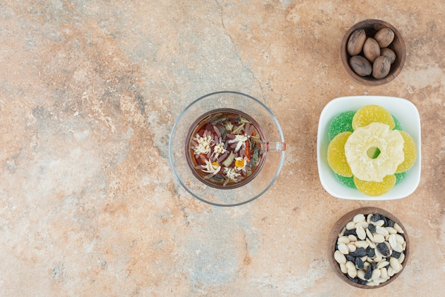 Un piatto bianco pieno di caramelle di gelatina di zucchero e una tazza di tisana