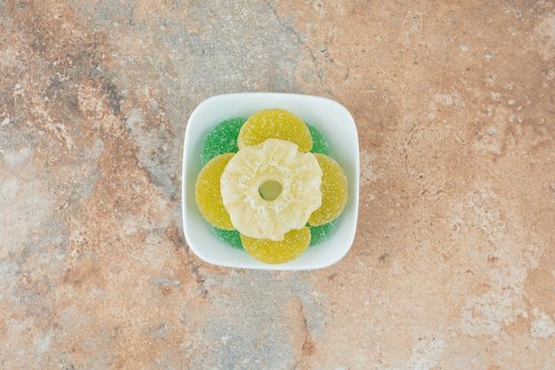 Un piatto bianco pieno di caramelle di gelatina di zucchero su fondo di marmo