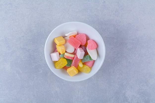 Un piatto bianco pieno di caramelle di gelatina zuccherate sulla superficie grigia