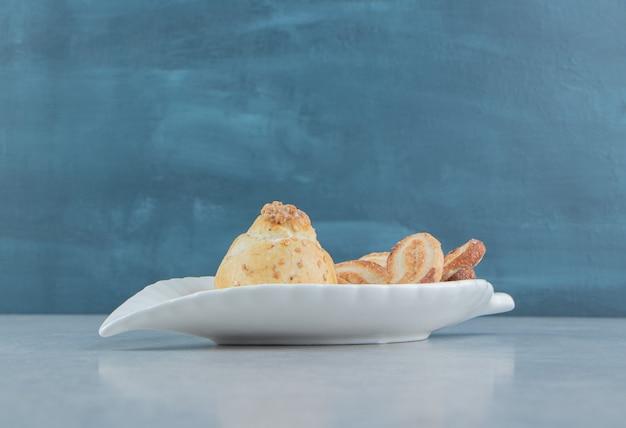 Un piatto bianco pieno di deliziosi biscotti dolci con lo zucchero.