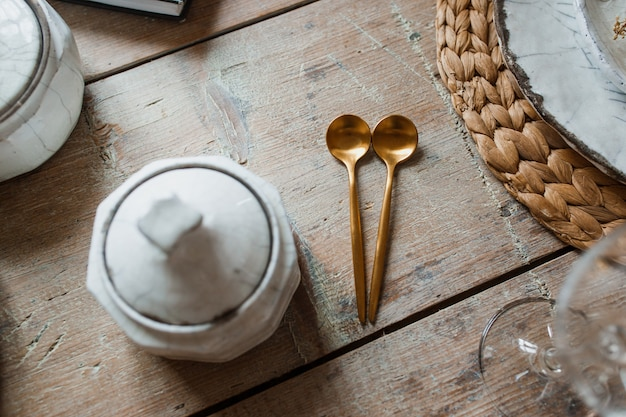 White plate and golden fork with a spoon, appliances for frying, wedding decoration