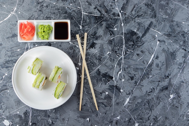White plate of green dragon sushi rolls on marble background.