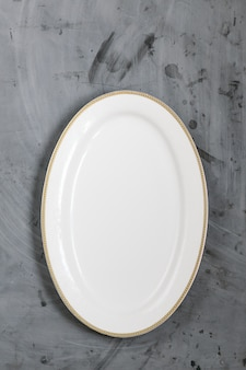 White plate on grey concrete background. copy space.