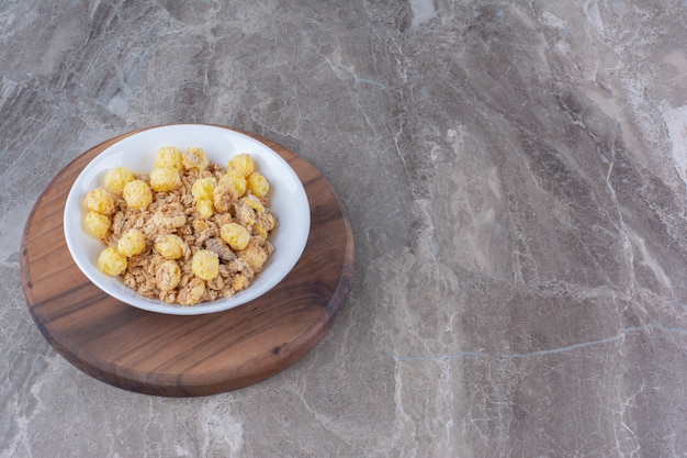 A white plate of healthy cornflakes on a wooden round board .