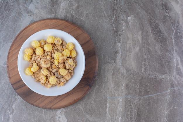 Un piatto bianco di fiocchi di mais sani su una tavola rotonda di legno.
