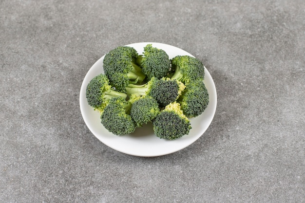 White plate of healthy fresh broccoli on stone table.