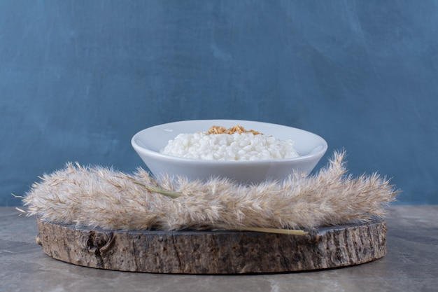A white plate of healthy oatmeal porridge on a wooden piece .