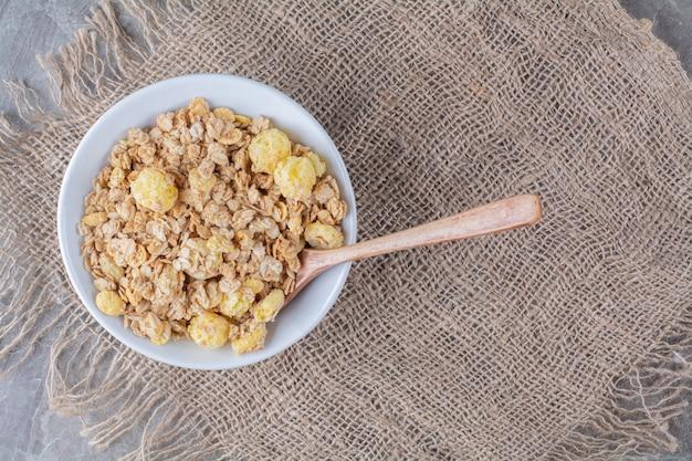 Un piatto bianco di sani fiocchi di mais dolci su una tela di sacco.