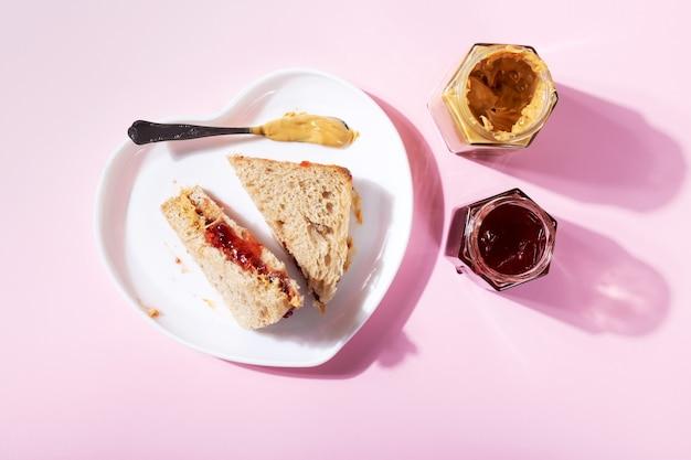 Белая тарелка в форме сердца с бутербродами с арахисовым маслом и клубничным желе на розовом фоне. вид сверху