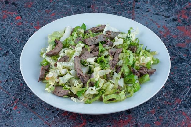 Un piatto bianco di carne con insalata di verdure.