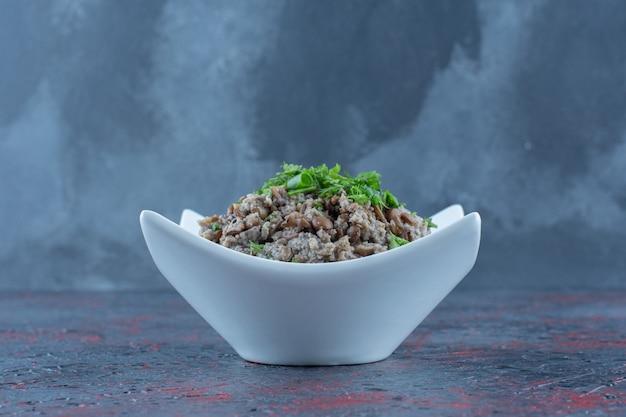 Un piatto bianco di carne tritata con piselli ed erbe aromatiche.