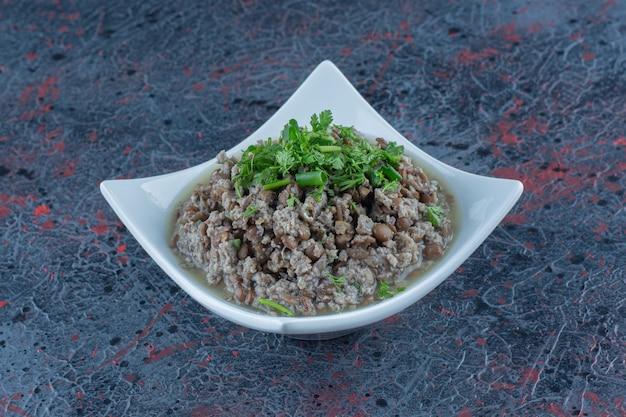 Un piatto bianco di carne tritata con piselli ed erbe aromatiche