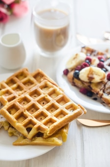 Белая тарелка бельгийских вафель с сахарной пудрой, замороженными ягодами, бананом и карамельным соусом
