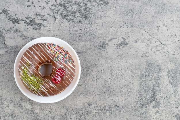 Белая тарелка пончика в шоколадной глазури на каменном фоне.