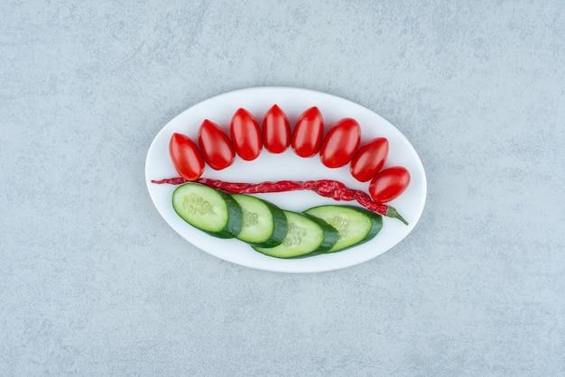 きゅうりのみじん切り、トマトチェリー、コショウの白皿。高品質の写真