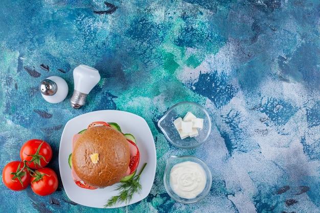 Белая тарелка вкусного гамбургера и помидоров на синей поверхности