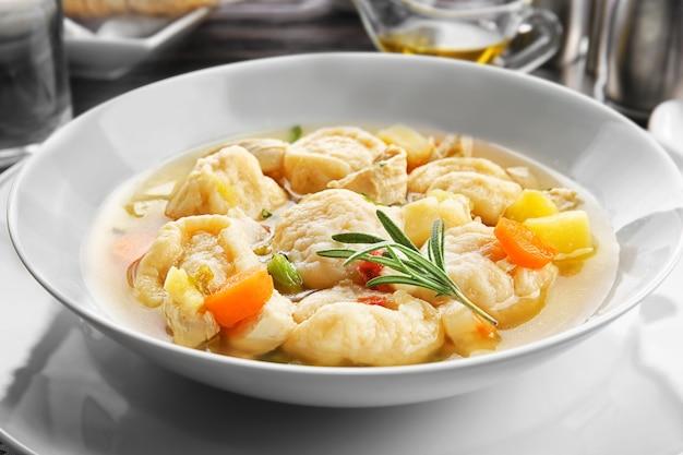 Белая тарелка вкусной курицы и пельменей крупным планом