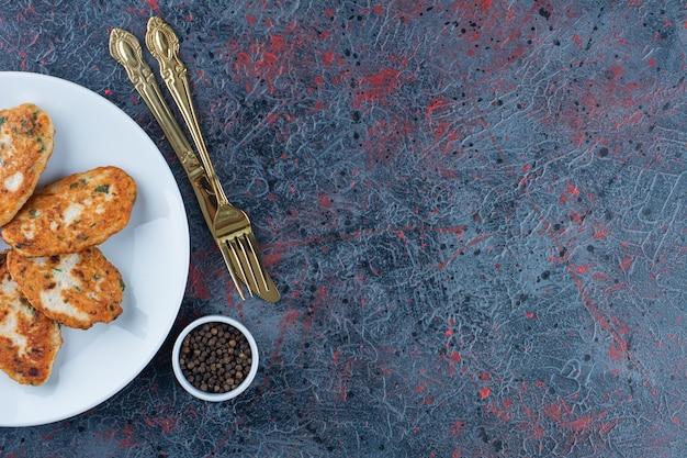 대리석 표면에 맛있는 치킨 cutlets의 흰색 접시.