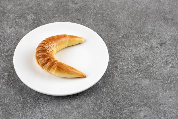大理石のテーブルにおいしい三日月形のバニラクッキーの白いプレート。