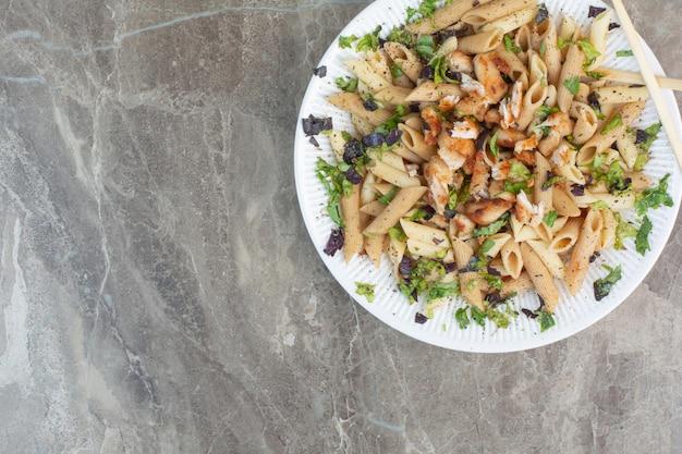 Белая тарелка вкусных макарон с палочками для еды.
