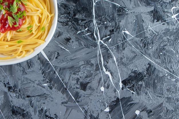 Белая тарелка вкусных спагетти с томатным соусом на мраморной поверхности.