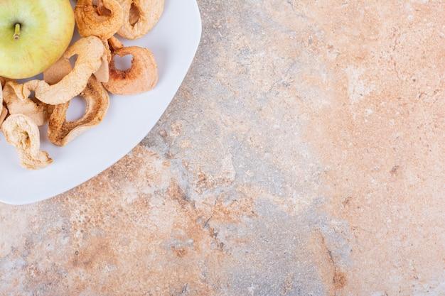 대리석 테이블에 마른 사과 고리와 신선한 녹색 사과의 흰색 접시. 고품질 사진