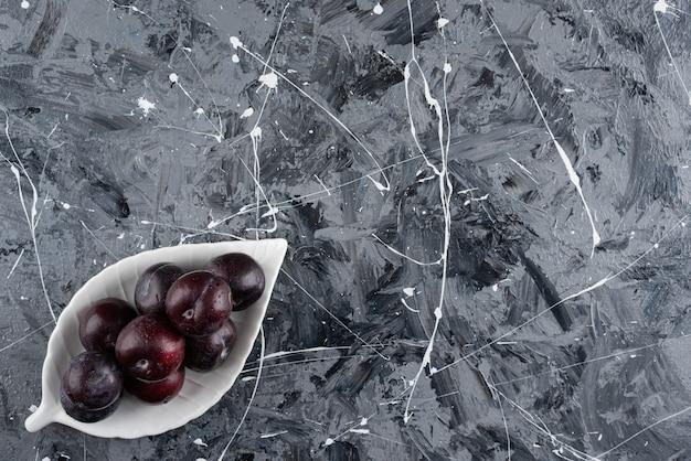 大理石の表面に新鮮な紫色のプラムの白いプレート。