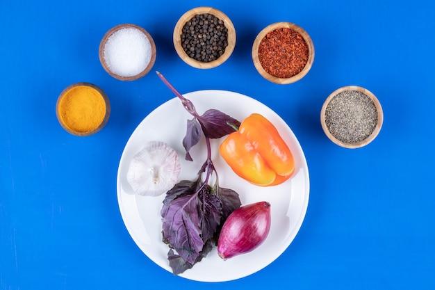 푸른 표면에 신선한 야채와 향신료의 흰색 접시