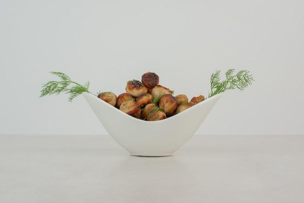 야채와 함께 튀긴 된 감자의 흰 접시입니다.