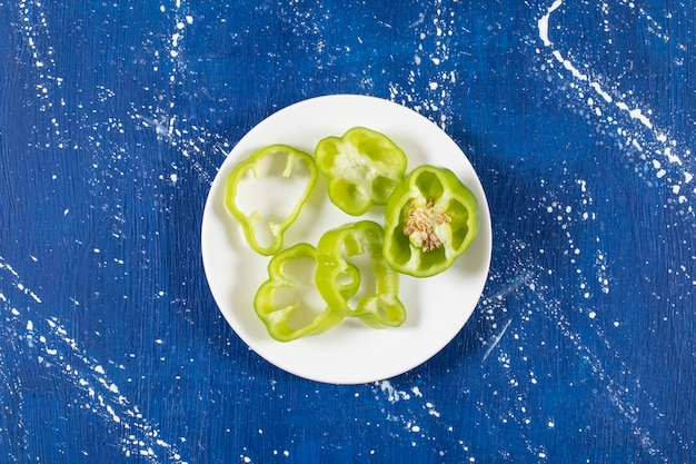 Белая тарелка зеленых колец болгарского перца на мраморной поверхности.