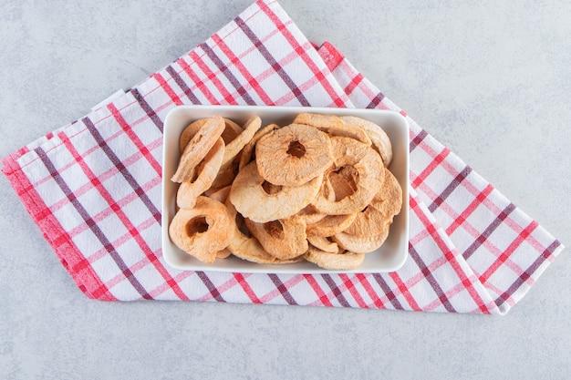 돌 배경에 건강에 좋은 말린 사과 반지의 흰색 접시.