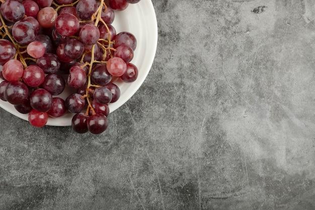 大理石のテーブルに白いプレートとレッドデリシャスのブドウ。