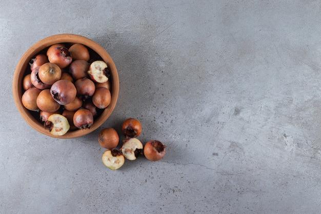 Белая тарелка спелых плодов мушмулы на каменном столе.
