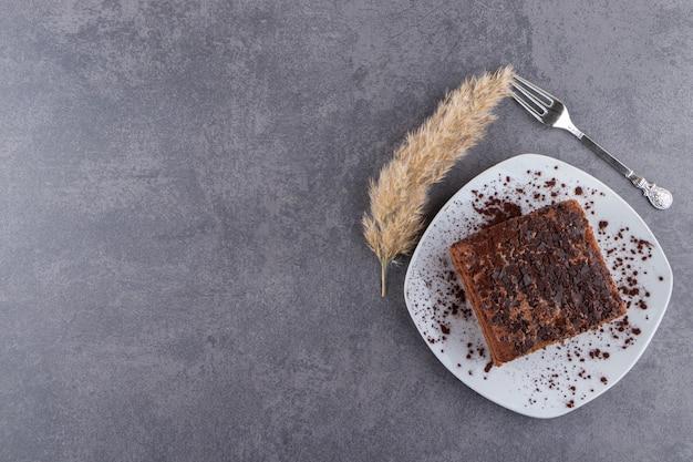 돌 테이블에 달콤한 슬라이스 케이크의 흰색 접시.