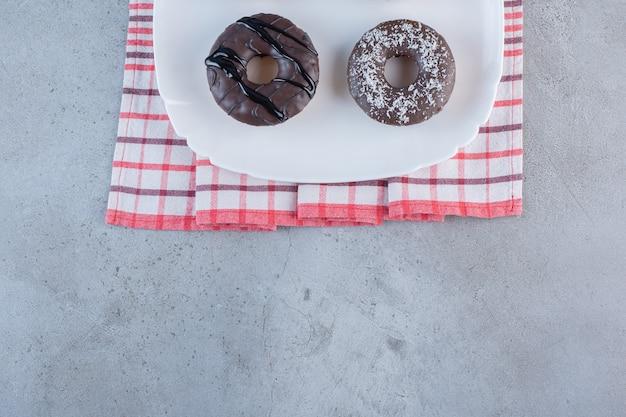 돌에 맛 있는 초콜릿 도넛의 흰색 접시입니다.