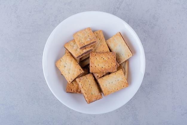 Белая тарелка вкусных хрустящих крекеров на каменном столе.