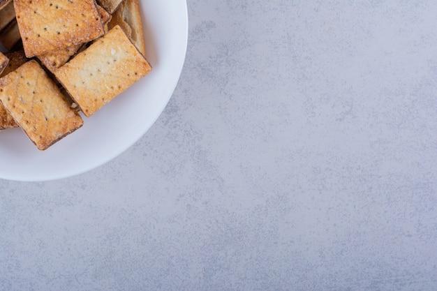 돌에 맛 있는 바삭바삭한 크래커의 흰색 접시입니다.