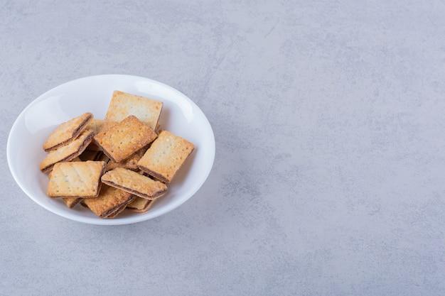 Белая тарелка вкусных хрустящих крекеров на камне.