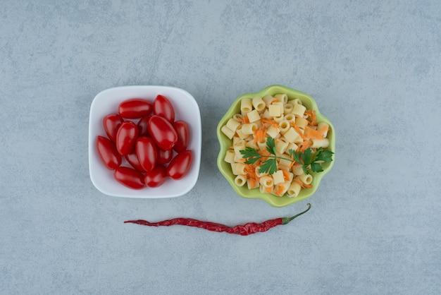 トマトチェリーの白皿と美味しいマカロニの緑皿。高品質の写真