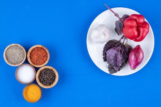 Белая тарелка помидоров, чеснока и лука на синей поверхности.