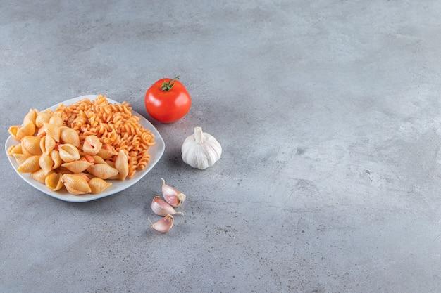Белая тарелка двух различных сливочных макарон на каменном фоне.