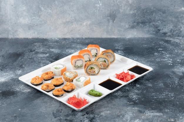 Белая тарелка различных вкусных суши-роллов на мраморном фоне