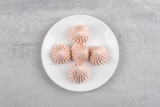 돌 테이블에 흰 머 랭 디저트의 흰 접시.