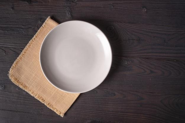 Белая тарелка на желтой салфетке на деревянном столе, вид сверху, место для меню или рецепта.
