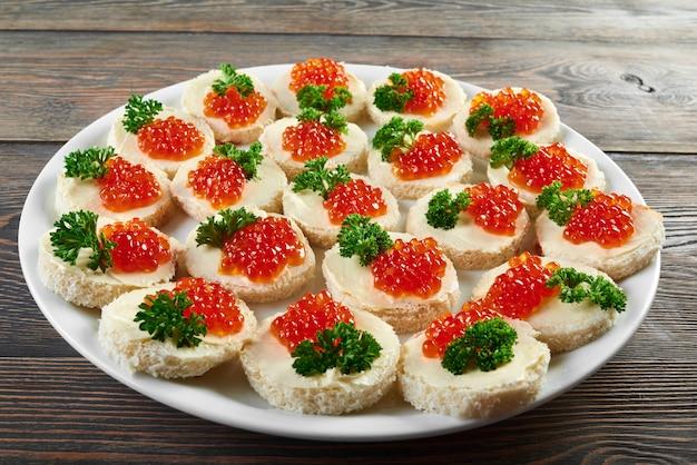 Белая тарелка на деревянном столе, полная маленьких канапе с маслом, красной икрой и украшенная свежими зелеными листьями петрушки. вкусная закуска из кейтеринга или ресторанного шведского стола