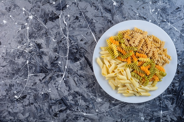 A white plate of raw dry multi colored fusilli pasta with penne macaroni
