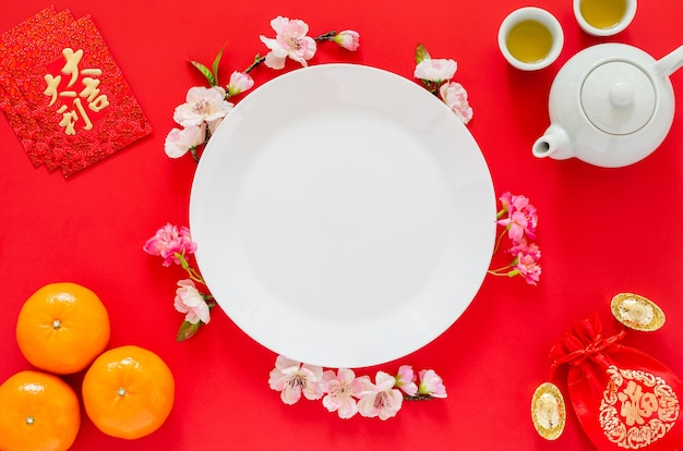 White plate on red background with tea set, gold ingots, red bag (word means wealth), ornages, red envelope packets or ang bao(word means auspice) and chinese blossom flowers for chinese new year.