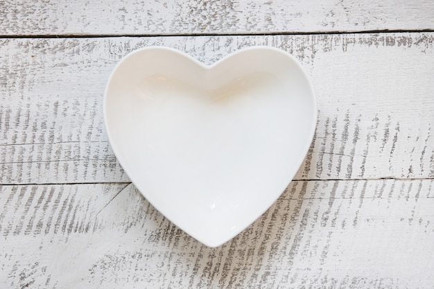 White plate in shape of heart on wooden vintage table. top view.