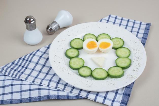 Un piatto bianco di cetriolo affettato e uovo sodo.