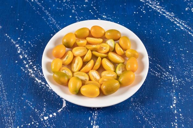 Piatto bianco di frutti di kumquat freschi a fette su superficie di marmo